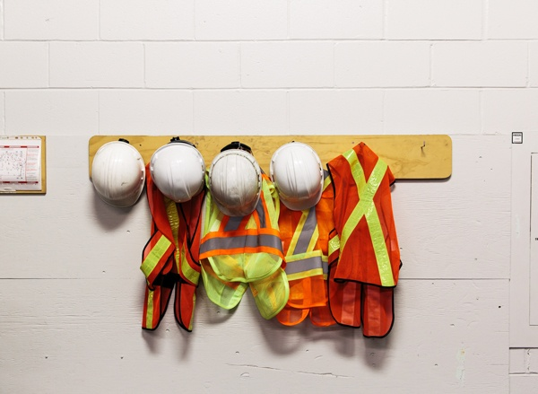 Safety hard hats and reflective vests hung up on pegs
