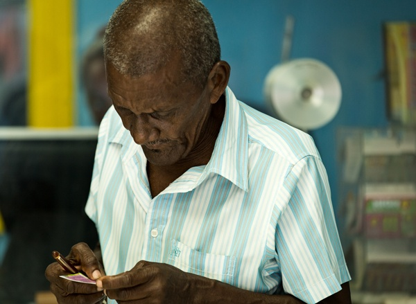 Local, elderly St.Lucian man checks lottery ticket