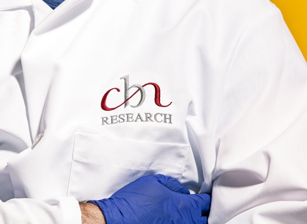Part of CBN employees lab coat with 'CBN Research' embroidered on it